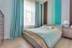 Гостевая спальня с деревянной стеной у изголовья