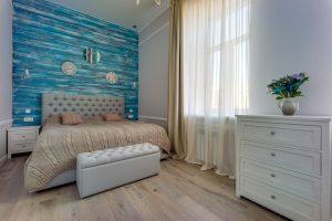 Спальня с синей деревянной стеной у изголовья кровати